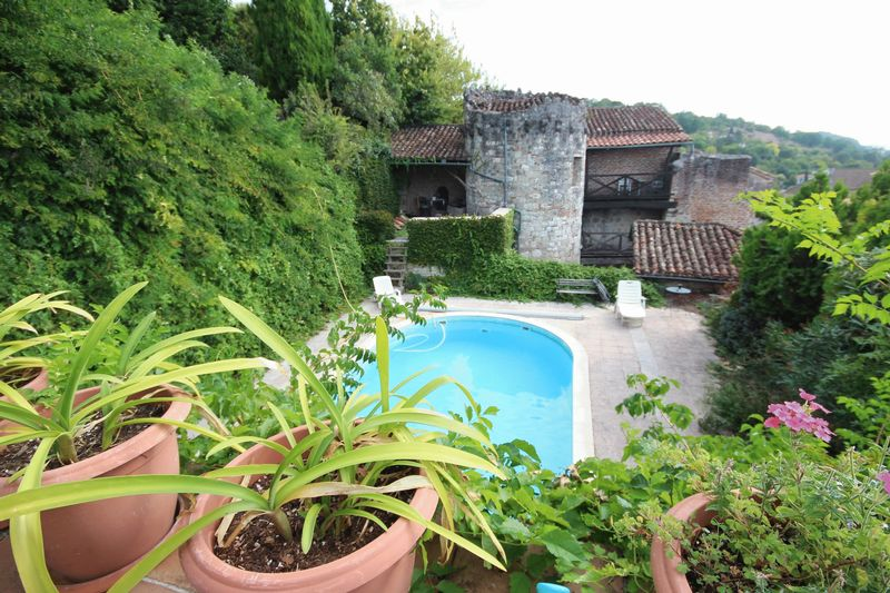 Stone properties in village with 13th century tower large terraced gardens and pool