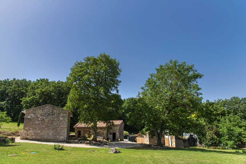 Magnificent hamlet of several stone houses in a green setting with truffle oaks.